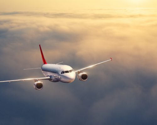 Airplane is flying above the clouds at sunset in summer. Landscape with passenger airplane, low clouds, orange sky. Top view of the aircraft. Business travel. Commercial plane. Aerial view. Take off