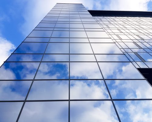 Grodno, Belarus - 03.22.2021: View of a modern glass skyscraper. Reflection of a cloudy blue sky in a glass skyscraper